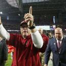 FILE - In this Nov. 16, 2014, file photo, Arizona Cardinals coach Bruce Arians, center, raises his arms as he celebrates with fans as he is flanked by Cardinals general manager Steve Keim, right, and team president Michael Bidwill, left, after an NFL football game against the Detroit Lions in Glendale, Ariz. Arians has won The Associated Press NFL Coach of the Year award. (AP Photo/Ross D. Franklin, File)