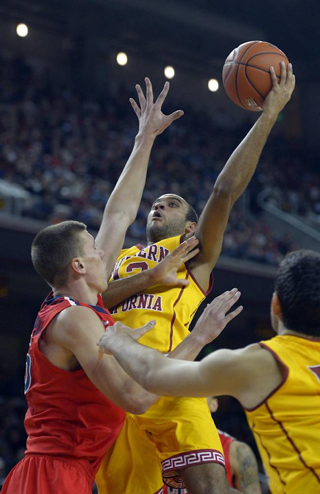 Southern California guard Julian Jacobs, center, puts up a shot as Arizona center Kaleb Tarczewski defends during the second half of an NCAA college basketball game, Sunday, Jan. 12, 2014, in Los Angeles