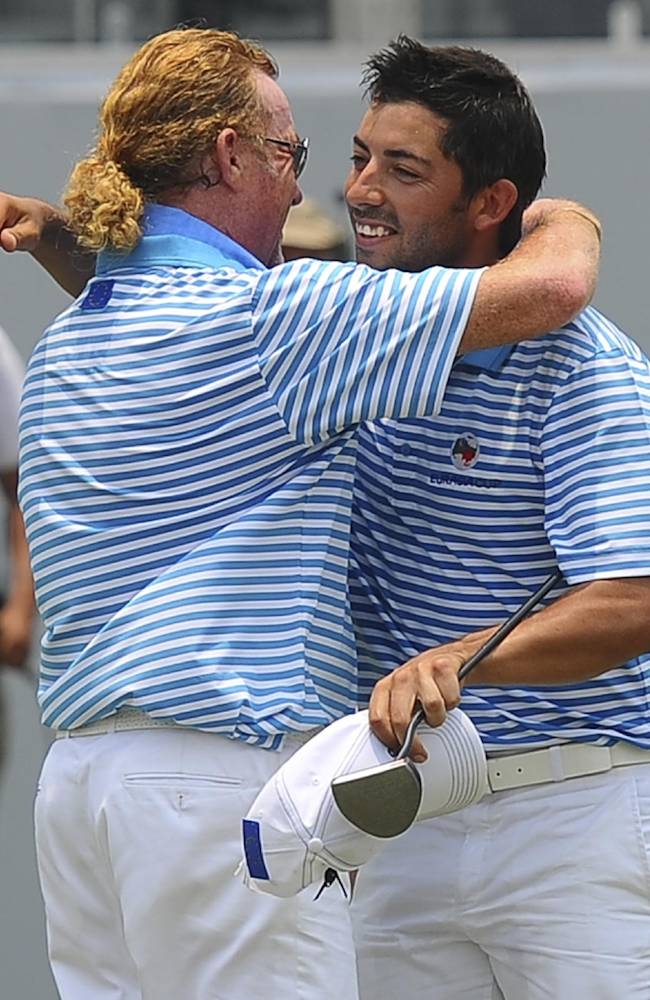 Miguel Angel Jimenez, left, of Spain hugs compatriot Pablo Larrazabal after he sunk a birdie putt to secure a draw at the eighteenth hole during the second round of the EurAsia Cup golf tournament at the Glenmarie Golf and Country Club in Subang, Malaysia, Friday, March 28, 2014