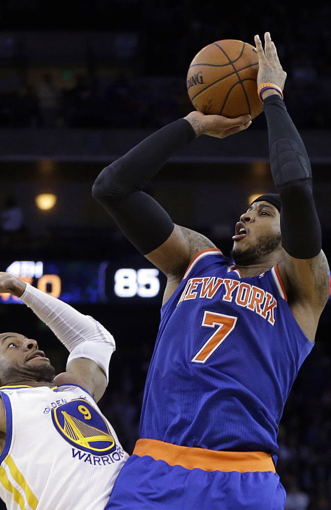 New York Knicks' Carmelo Anthony (7) shoots over Golden State Warriors' Andre Iguodala, left, during the second half of an NBA basketball game Sunday, March 30, 2014, in Oakland, Calif