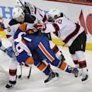 New York Islanders center Mikhail Grabovski (84) is knocked off his feet by New Jersey Devils Seth Helgeson (45) and Peter Harrold (10) in the third period of a preseason NHL hockey game Friday, Sept. 26, 2014, in New York. The Islanders won 3-2 in a shootout. (AP Photo/Paul Bereswill)