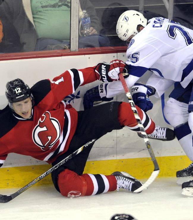 Tampa Bay Lightning's Matthew Carle, right, checks New Jersey Devils' Damien Brunner, of Switzerland, during the third period of an NHL hockey game Tuesday, Oct. 29, 2013, in Newark, N.J. The Devils defeated the Lightning 2-1