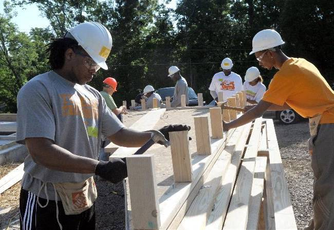 In this photo taken on June 2, 2012, Tennessee men's basketball strength coach Nicodemus Christopher, left, works on a Habitat for Humanity house in Knoxville, Tenn. The in-state rivalry between Tennessee and Vanderbilt now includes a sibling rivalry The strength coaches at the respective programs are brothers: Nicodemus Christopher at Tennessee and Garry Christopher at Vanderbilt. They'll reunite Wednesday with plenty of family members in the Memorial Gym stands