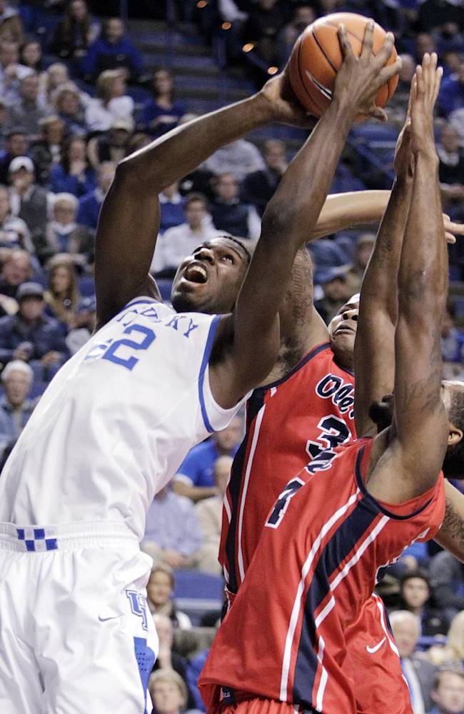 Kentucky's Alex Poythress, left, looks for an opening on Ole Miss' Jarvis Summers and Aaron Jones, right, during the first half of an NCAA college basketball game, Sunday, Feb. 4, 2014, in Lexington, Ky