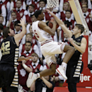 Indiana's Troy Williams (5) puts up a shot against Oakland's Travis Bader, right, and Corey Petros (42) during the first half of an NCAA college basketball game Tuesday, Dec. 10, 2013, in Bloomington, Ind. (AP Photo/Darron Cummings)
