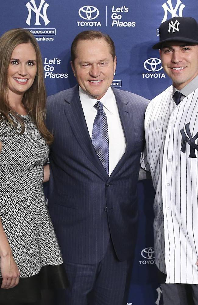 Jacoby Ellsbury, right, and his wife Kelsey, left, pose for a photograph with sports agent Scott Boras following a news conference at Yankee Stadium, Friday, Dec. 13, 2013, in New York. Ellsbury, the former Boston Red Sox outfielder, agreed to a $153 million seven-year contract with the Yankees