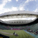 The roof on Centre Court is moved into place while grounds crew members attend to the grass after matches concluded at the All England Lawn Tennis Club in Wimbledon, London at the 2012 Summer Olympics, Thursday, Aug. 2, 2012. (AP Photo/Elise Amendola)