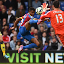 Crystal Palace's Fraizer Campbell, center, competes for the ball with Chelsea's Thibaut Courtois, right, as Chelsea's Gary Cahill looks on during their English Premier League soccer match at Selhurst Park, London, Saturday, Oct. 18, 2014