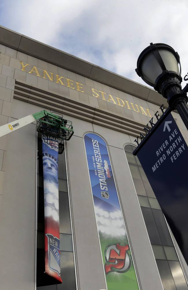 Workers hang banners outside New York's Yankee Stadium, Saturday, Jan. 18, 2014 ,for NHL Stadium Series games. The stadium will host the New York Rangers and New Jersey Devils on Jan. 26 and the Rangers-New York Islanders on Jan. 29