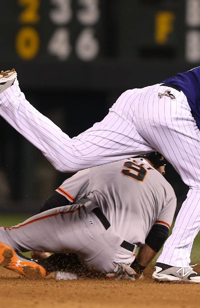 Colorado Rockies second baseman DJ LeMahieu, top, forces out San Francisco Giants' Brandon Belt at second base on the front end of a double play hit into by Brandon Hicks in the fourth inning of a baseball game in Denver on Monday, April 21, 2014