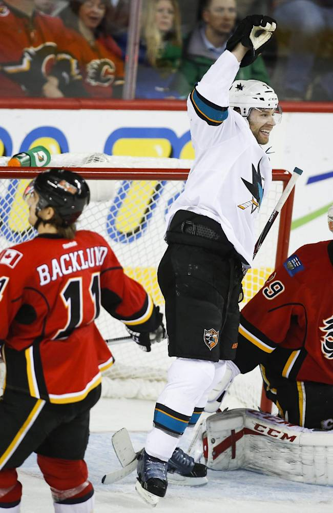 San Jose Sharks' Brad Stuart, center, celebrates his game-winning goal as Calgary Flames goalie Reto Berra, right, from Switzerland, looks away and Mikael Backlund, from Sweden, skates away during overtime in an NHL hockey game in Calgary, Alberta, Tuesday, Nov. 12, 2013. The Sharks won 3-2