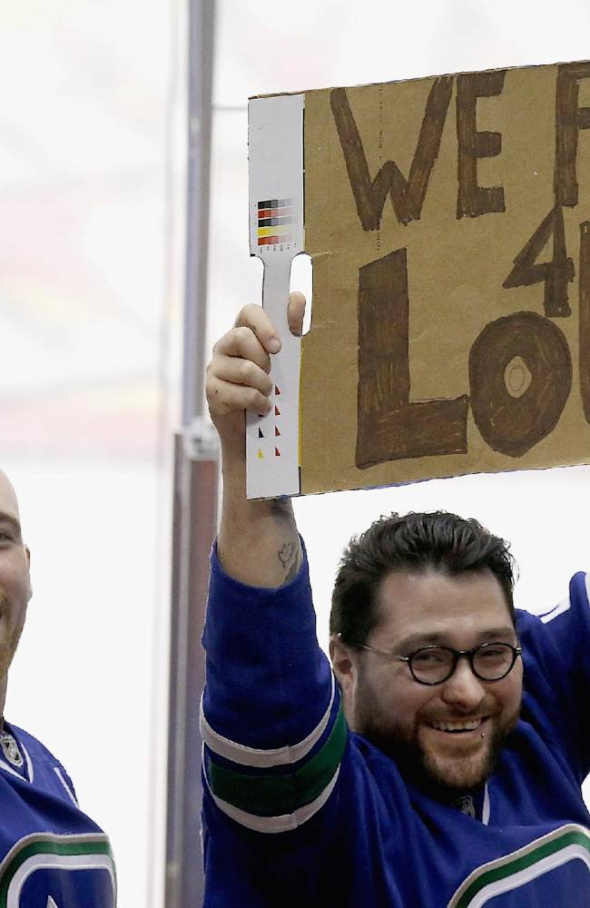 Vancouver Canucks fans make the best of it after learning goalie Roberto Luongo had been traded, as they stand up with a makeshift sign during the third period of an NHL hockey game against the Phoenix Coyotes on Tuesday, March 4, 2014, in Glendale, Ariz.  The Coyotes defeated the Canucks 1-0