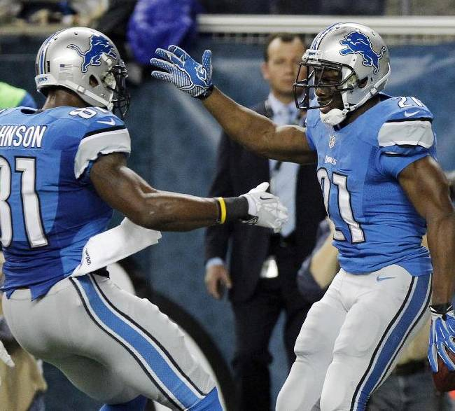 Detroit Lions wide receiver Calvin Johnson (81) congratulates running back Reggie Bush after Bush's 14-yard touchdown during the first quarter of an NFL football game against the Baltimore Ravens in Detroit, Monday, Dec. 16, 2013