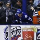 Los Angeles Kings' Colin Fraser lies on the ice after being hit by Toronto Maple Leafs Frazer McLaren as Maple Leafs' Morgan Rielly looks over the boards during second period NHL hockey action in Toronto Wednesday, Dec. 11, 2013. (AP Photo/The Canadian Press, Mark Blinch)
