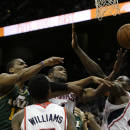 Utah Jazz power forward Derrick Favors (15), left, battles Atlanta Hawks' Paul Millsap (4) and Elton Brand (42), right, for a loose ball in the first half of an NBA basketball game on Friday, Dec. 20, 2013, in Atlanta. (AP Photo/John Bazemore)