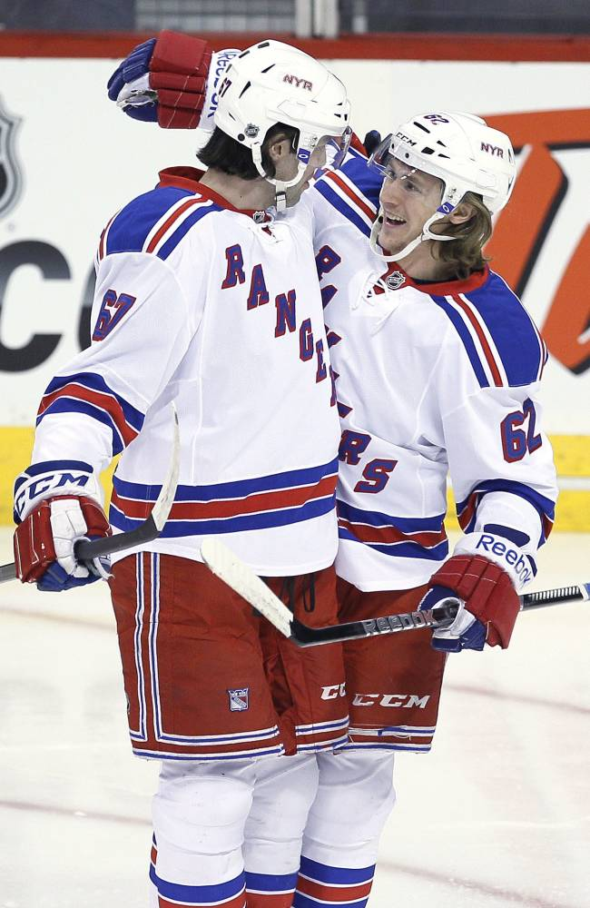 CORRECTS GOAL SCORER TO CARL HAGELIN- New York Rangers' Carl Hagelin (62) and Benoit Pouliot (67) celebrates Hagelin's goal against the Winnipeg Jets during first period NHL action in Winnipeg on Friday, March 14, 2014. THE CANADIAN PRESS/John Woods