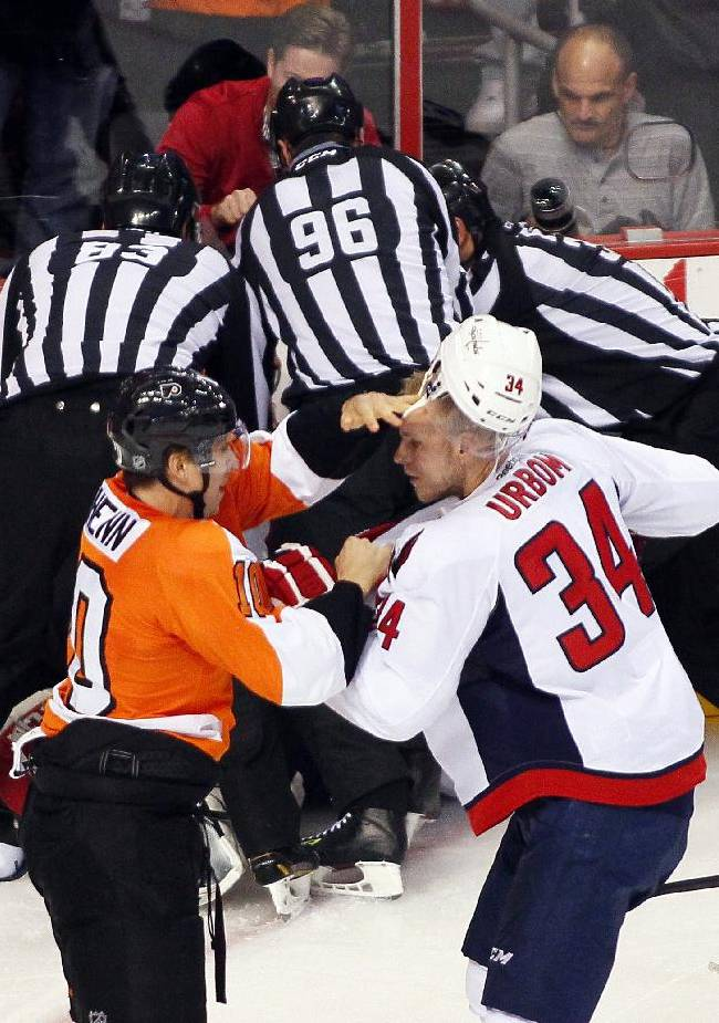 Philadelphia Flyers' Brayden Schenn, left, and Washington Capitals' Alexander Urbom, right, square off to fight as officials, rear, struggle to pull Flyers goalie Ray Emery off of Capital goalie Brayden Holtby during a melee in the third period of an NHL hockey game Friday, Nov. 1, 2013, in Philadelphia. The Capital won 7-0