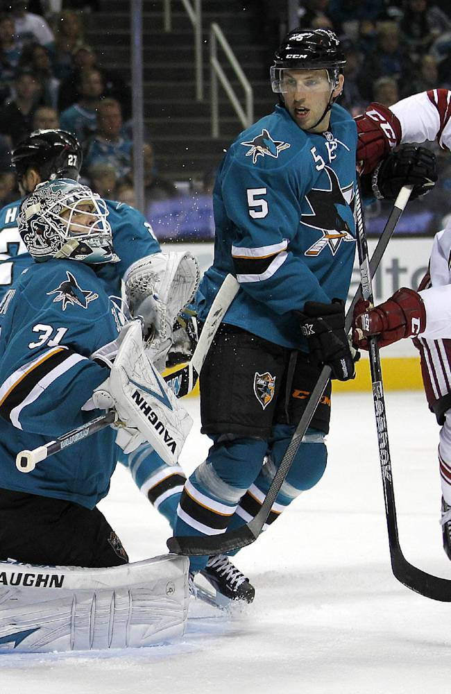 San Jose Sharks goalie Antti Niemi (31) block a goal attempt by Phoenix Coyotes left wing Rob Klinkhammer (36) as San Jose Sharks defenseman Jason Demers (5) defends  during the second period an NHL hockey game in San Jose, Calif., Saturday, Oct. 5, 2013