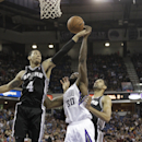 Sacramento Kings forward Reggie Evans, center, battles for the rebound between San Antonio Spurs' Danny Green, left, and Tim Duncan during the third quarter of an NBA basketball game in Sacramento, Calif., Friday, March 21, 2014. The Spurs won 99-79 The