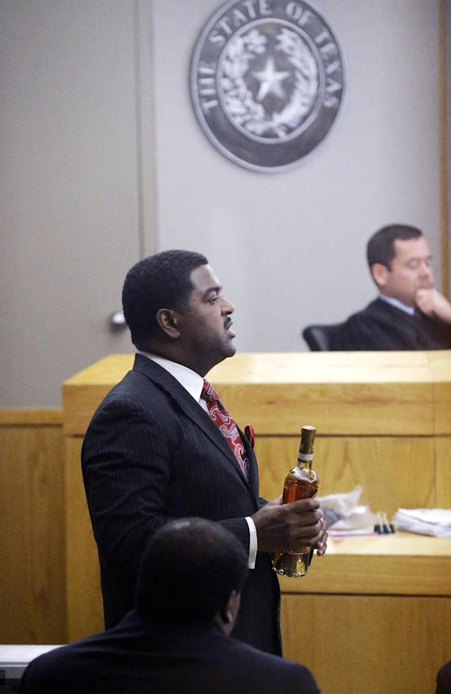 CORRECTS ID TO HEATH HARRIS, NOT JASON HERMUS - Prosecutor Heath Harris holds a bottle to make a point during closing arguments in former Dallas Cowboys NFL football player Josh Brent's intoxication manslaughter trial Tuesday, Jan. 21, 2014, in Dallas. Prosecutors accuse the former defensive tackle of drunkenly crashing his Mercedes near Dallas during a night out in December 2012, killing his good friend and teammate, Jerry Brown. Listening in brackground is Judge Robert Burns III