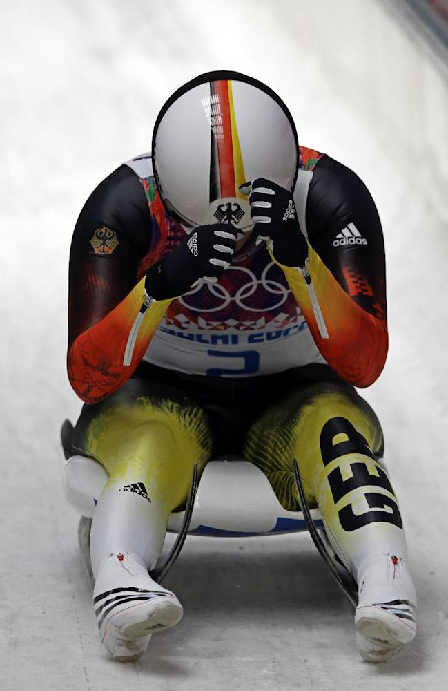 Natalie Geisenberger of Germany puts her head in her hands after finishing her final run to win the gold medal during the women's singles luge competition at the 2014 Winter Olympics, Tuesday, Feb. 11, 2014, in Krasnaya Polyana, Russia