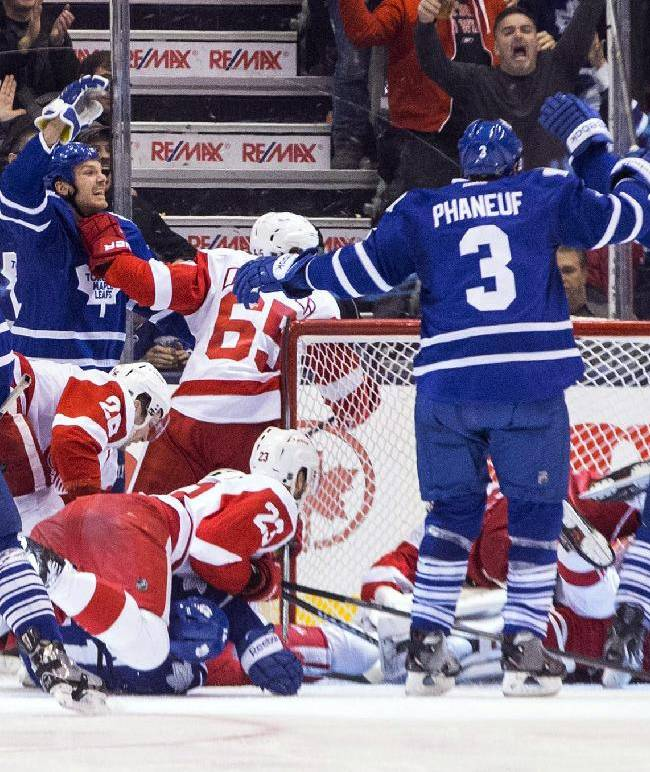 Toronto Maple Leafs Dave Clarkson, second from left, celebrates after scoring against the Detroit Red Wings during the third period of an NHL hockey game in Toronto on Saturday, Dec. 21, 2013
