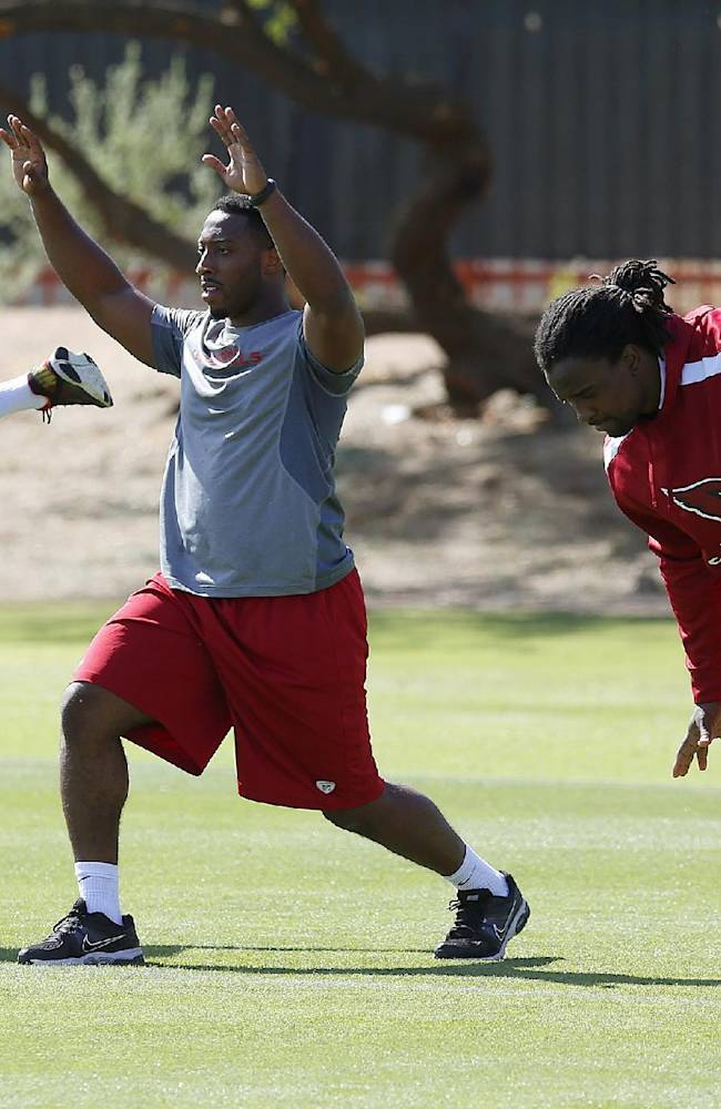 From left to right, Arizona Cardinals' Andre Ellington, Stepfan Taylor and Robert Hughes stretch as they work out with teammates during the first phase of the voluntary offseason training program at the NFL football team's training facility Thursday, April 24, 2014, in Tempe, Ariz