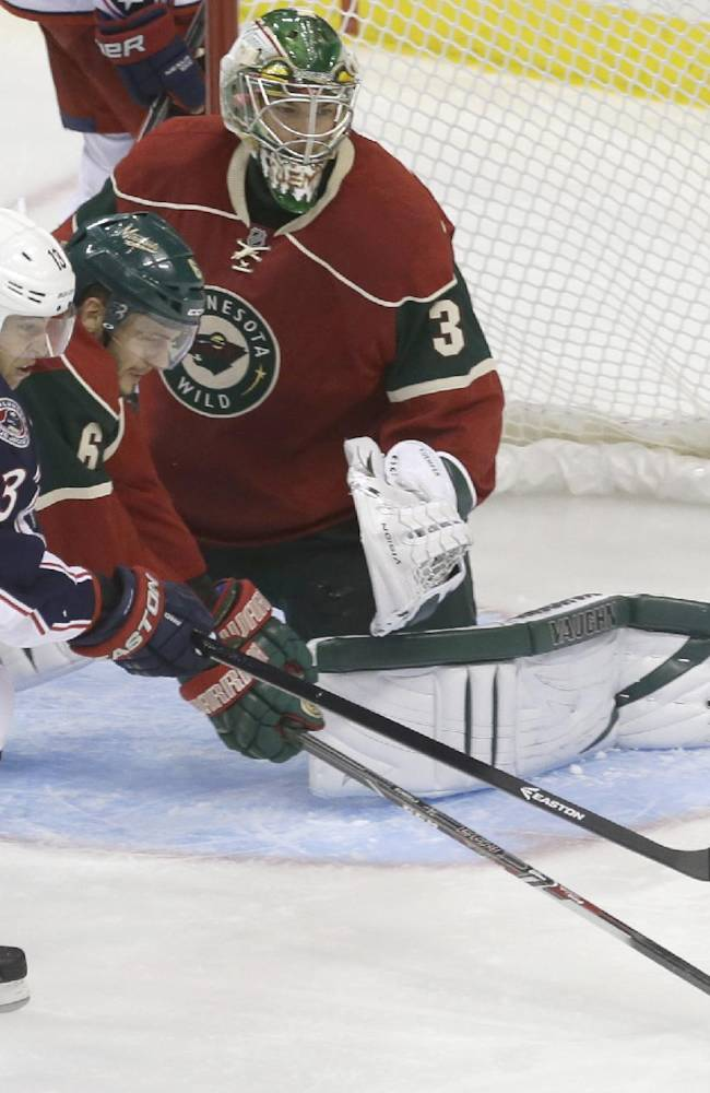 Minnesota Wild's Marco Scandella, second from left, breaks up a scoring attempt by Columbus Blue Jackets' Cam Atkinson, left, as goalie Darcy Kuemper defends the net in the third period of an NHL preseason hockey game, Tuesday, Sept. 17, 2013 in St. Paul. Minn. The Blue Jackets won 3-1