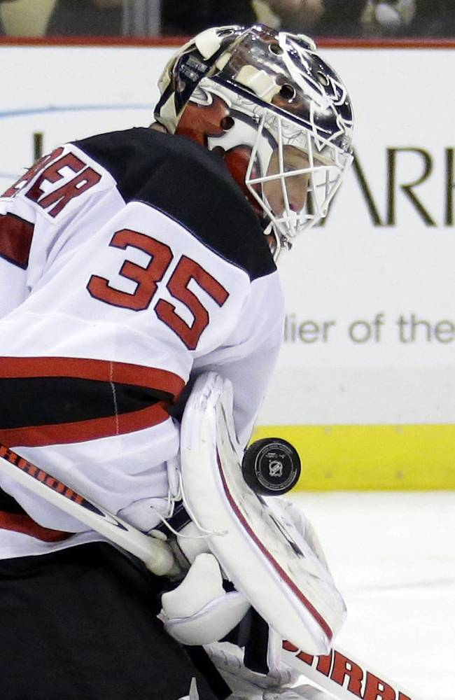 New Jersey Devils goalie Cory Schneider stops a shot in the second period of an NHL hockey game against the Pittsburgh Penguins in Pittsburgh, Friday, Dec. 13, 2013