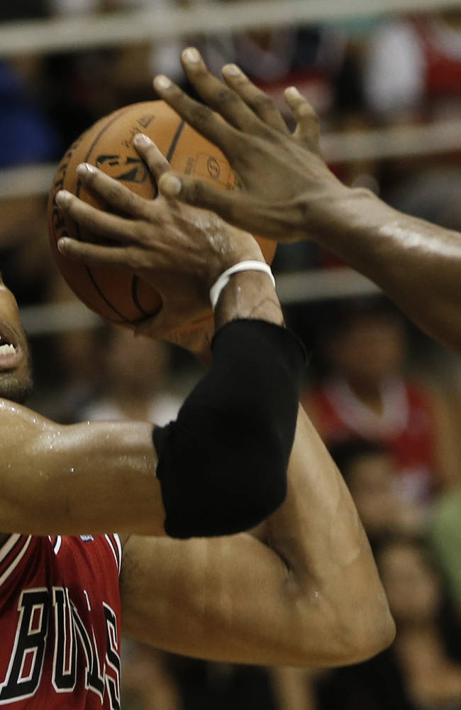 Chicago Bulls' Taj Gibson is blocked by Washington Wizards' Kevin Seraphin during the first half of an NBA preseason basketball game in Rio de Janeiro, Brazil, Saturday, Oct. 12, 2013