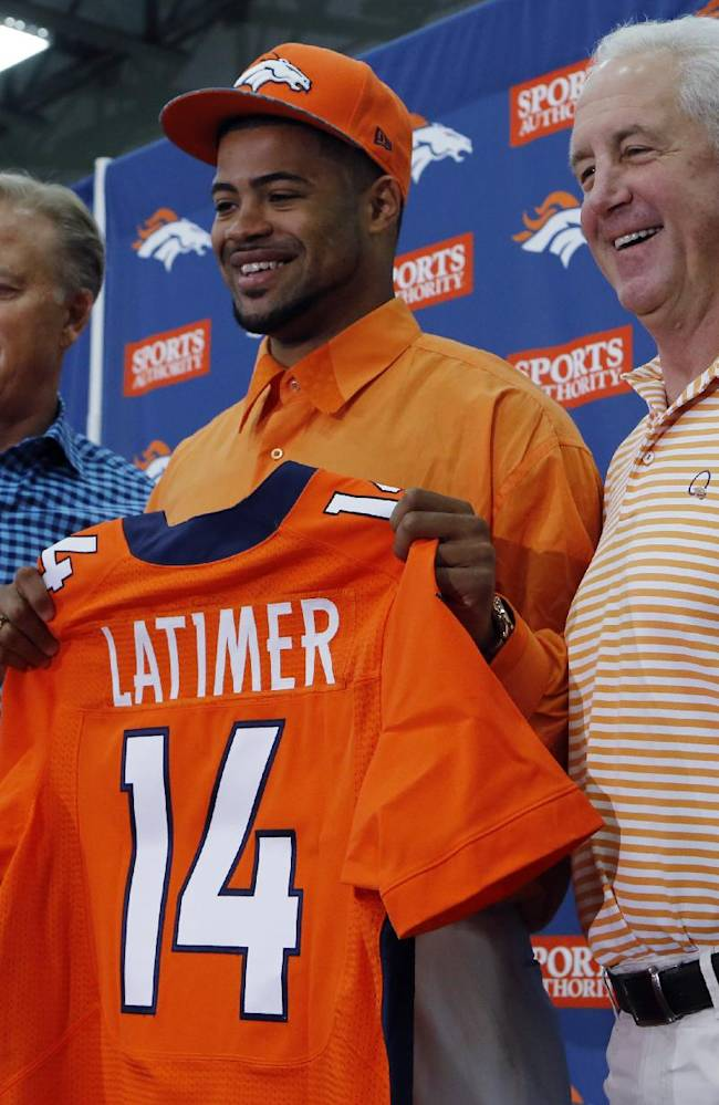 Denver Broncos vice president John Elway,left,  head coach John Fox, right, flank the Broncos second round draft pick Indiana wide receiver Cody Latimer as he is introduced to the media at the NFL football teams headquarters in Englewood, Colo., on Saturday, May 10, 2014