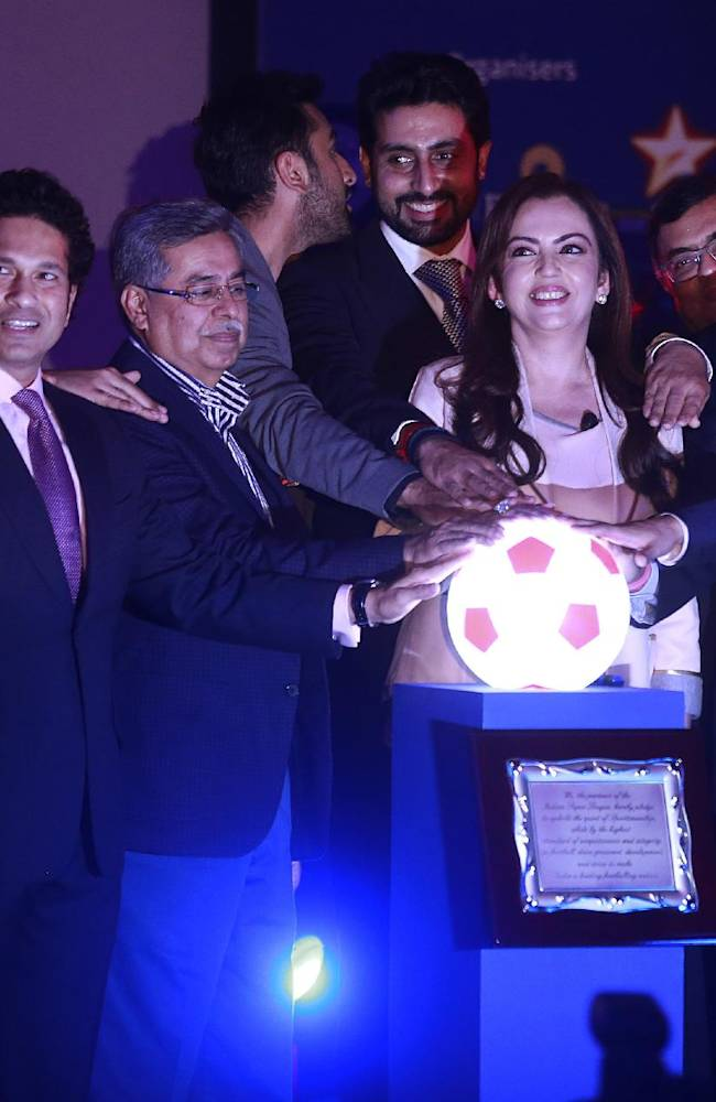 Reliance Foundation Chairman Nita Ambani, front third right, and All India Football Federation President Praful Patel, second right, along with co-owners of eight franchises from around the country, stand together for a photograph during the official launch of the Indian Super League (ISL) in Mumbai, India, Thursday, Aug. 28, 2014. The ISL, an initiative to popularize soccer in the country, is scheduled to begin Oct. 12