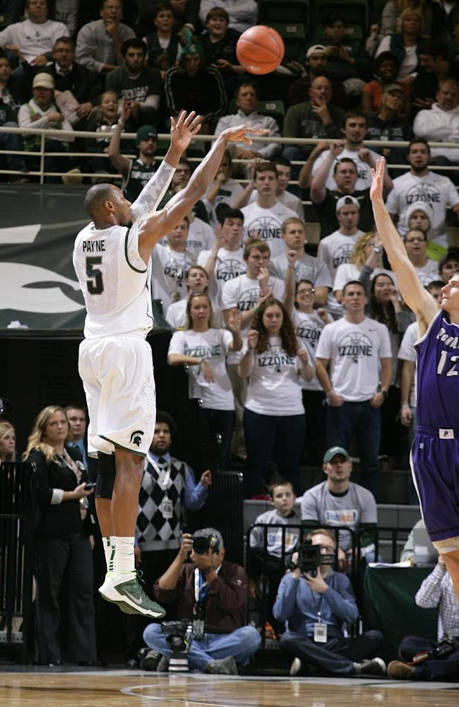 Michigan State's Adreian Payne (5) shoots a three-pointer against Portland Thomas Van Der Mars (12) during the first half of an NCAA college basketball game, Monday, Nov. 18, 2013, in East Lansing, Mich