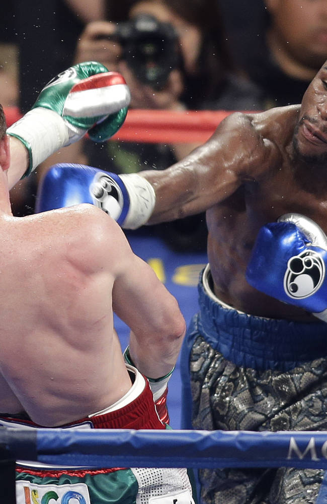 Floyd Mayweather Jr. throws a punch against Canelo Alvarez during a 152-pound title fight, Saturday, Sept. 14, 2013, in Las Vegas