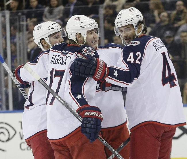 Columbus Blue Jackets center Brandon Dubinsky (17) celebrates with Artem Anisimov (42) and other teammates after scoring a goal during the first period of an NHL hockey game against the New York Rangers, Monday, Jan. 6, 2014, in New York