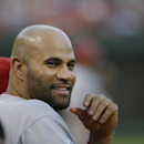 Los Angeles Angels designated hitter Albert Pujols smiles while sitting in the dugout with teammates during the eighth inning of a baseball game against the Texas Rangers in Arlington, Texas, Sunday, July 5, 2015. Pujols hit his AL-leading 25th home run, in the 12-6 win over the Rangers. (AP Photo/LM Otero)