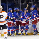 New York Rangers players celebrate a goal by teammate Ryan Haggerty, second from right, during the first period of an NHL preseason hockey game against the Philadelphia Flyers, Monday, Sept. 29, 2014, in New York. (AP Photo/Jason DeCrow)