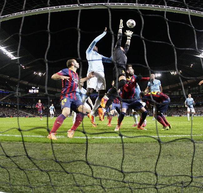 Barcelona goalkeeper Victor Valdes jumps for the ball next to Manchester City's Yaya Toure, during their Champions League first knock out round soccer match at the Etihad Stadium, Manchester, England, Tuesday Feb. 18, 2014
