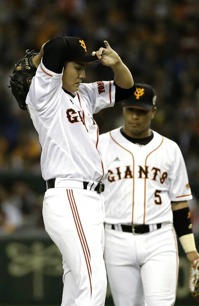 Yomiuri Giants starter Toshiya Sugiuchi, front, adjusts his cap as first baseman Javier Lopez approaches the mound after Sugiuchi gave up four runs against the Rakuten Eagles, in the fourth inning of Game 3 of baseball's Japan Series at Tokyo Dome in Tokyo, Tuesday, Oct. 29, 2013