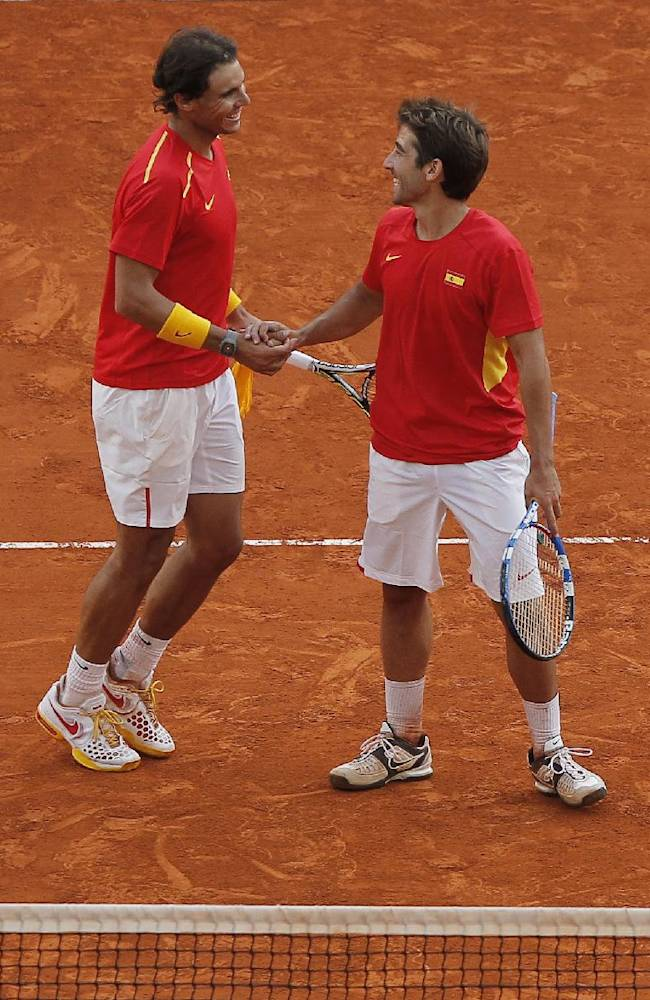 Spain's Rafael Nadal, left, and Marc Lopez, right, celebrate their victory during the doubles match against Ukraine's Denys  Molchanov and Sergiy Stakhovsky on the second day of the World Group play-off Davis Cup tennis in Madrid, Spain, Saturday, Sept. 14, 2013