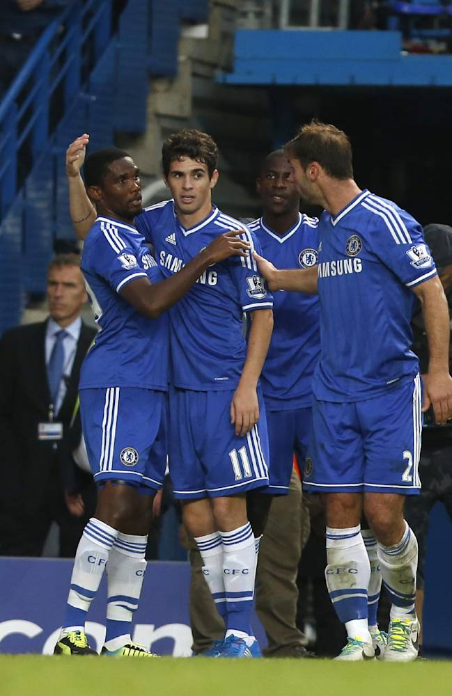 Chelsea's Oscar, centre, celebrates with teammates after scoring a goal against Fulham during the English Premier League soccer match between Chelsea and Fulham at Stamford Bridge, London, Saturday, Sept. 21, 2013