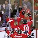 Chicago Blackhawks' Antoine Vermette, left, celebrates his goal with Patrick Sharp (10) and Teuvo Teravainen during the second overtime against the Anaheim Ducks in Game 4 of the Western Conference finals of the NHL hockey Stanley Cup playoffs, Saturday, May 23, 2015, in Chicago. The Blackhawks won 5-4. (AP Photo/Charles Rex Arbogast)