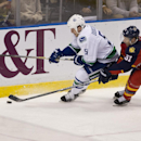 Vancouver Canucks' Derek Dorsett (51) and Florida Panthers' Brian Campbell (51) chase the puck during the second period of an NHL hockey game in Sunrise, Fla., Monday, Jan. 19, 2015 The Associated Press