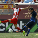 IMAGE DISTRIBUTED FOR GUINNESS INTERNATIONAL CHAMPIONS CUP - Manchester City midfielder David Silva, right, kicks the ball past Olympiacos defender Charalambos Lykogiannis, left, during the second half of 2014 Guinness International Champions Cup, on Satu
