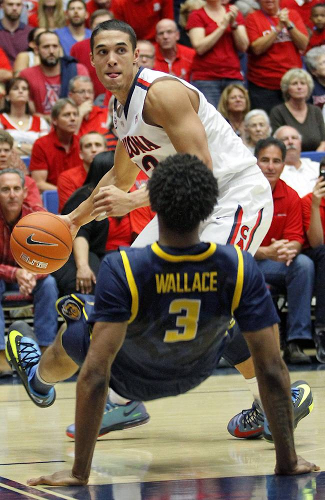 Arizona's Nick Johnson, in back, looks to pass over California's Tyrone Wallace (3) as he falls to the floor in the second half of an NCAA college basketball game on Wednesday, Feb. 26, 2014 in Tucson, Ariz. Arizona won 87 - 59