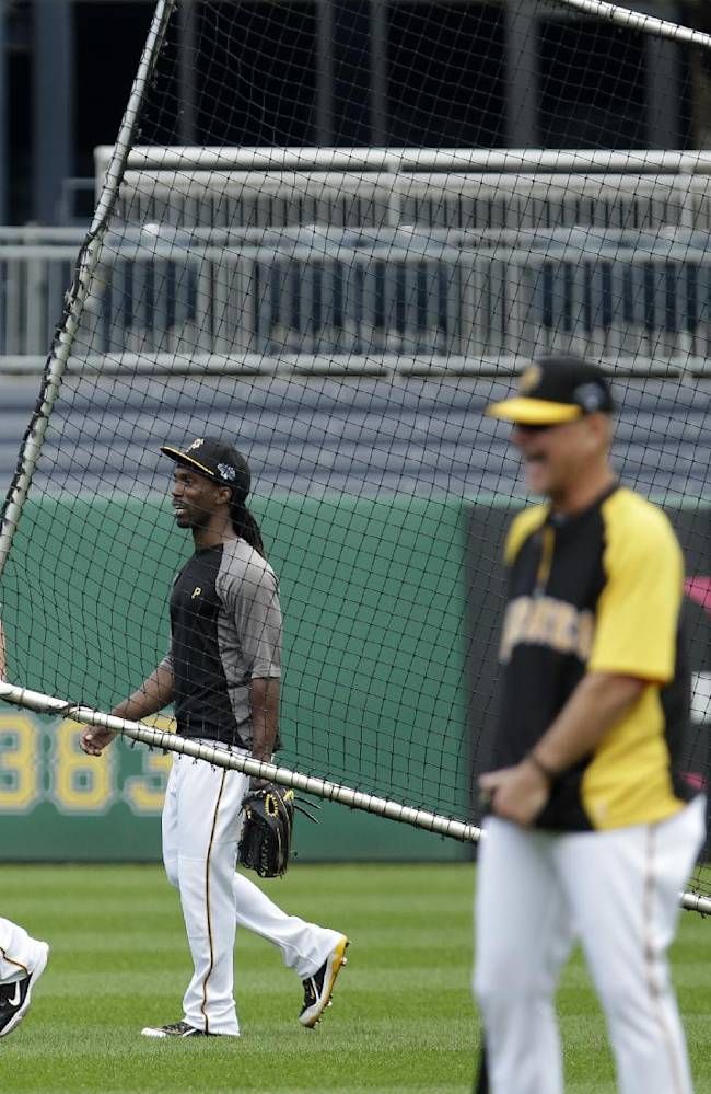 Pittsburgh Pirates manager Clint Hurdle, right, watches as Pirates catcher John Buck , left, pulls a protective batting practice screen in front of teammate Andrew McCutchen, second from left, as McCutchen walks off the field after being hit in the face by a batting practice line drive by Pirates' Jordy Mercer during the baseball team's workout in Pittsburgh Monday, Sept. 30, 2013. McCutchen did not return to the workout. The Pirates face the Cincinnati Reds in the National League Wild Card game Tuesday in Pittsburgh