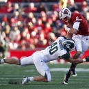 Wisconsin quarterback Joel Stave is tackled by Michigan State linebacker Max Bullough (40) during the first half of an NCAA college football game Saturday, Oct. 27, 2012, in Madison, Wis. (AP Photo/Andy Manis)