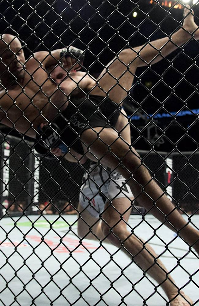 Demetrious Johnson, of the United States, left, gets thrown by Ali Bagautinov, of Russia, during the flyweight bout at UFC 174 in Vancouver, British Columbia, Saturday, June, 14, 2014