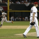 Arizona Diamondbacks' Addison Reed (43) walks back to pitcher's mound after giving up a two-run home run to San Francisco Giants' Buster Posey, left, during the ninth inning of an opening day baseball game, Monday, March 31, 2014, in Phoenix The Associate