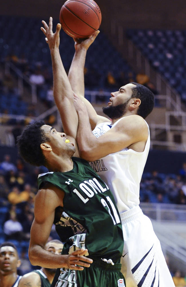 West Virginia's Remi Dibo (right) looks to shoot over Loyola Maryland's Jarred Jones (21) during the second half of an NCAA college basketball game Monday, Dec. 2, 2013, in Morgantown, W.Va. West Virginia won 96-47